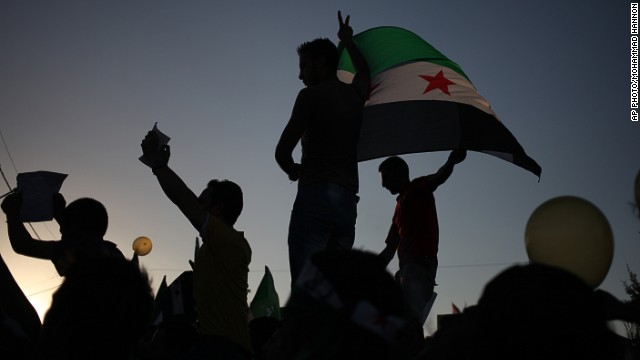 Syrian protesters waves the Syrian revolutionary flag and victory signs , during a protest in front of the Syrian embassy to condemn the alleged poison gas attack on the suburbs of Damascus, during a protest in front of the Syrian embassy, in Amman, Jordan, Friday, Aug. 23, 2013.