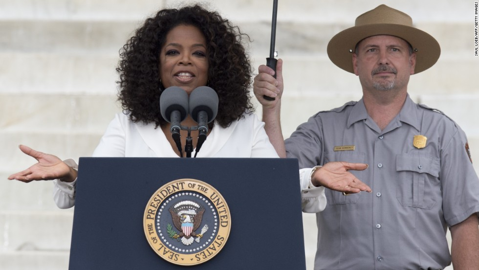 A park ranger holds an umbrella as Oprah Winfrey speaks during the event.