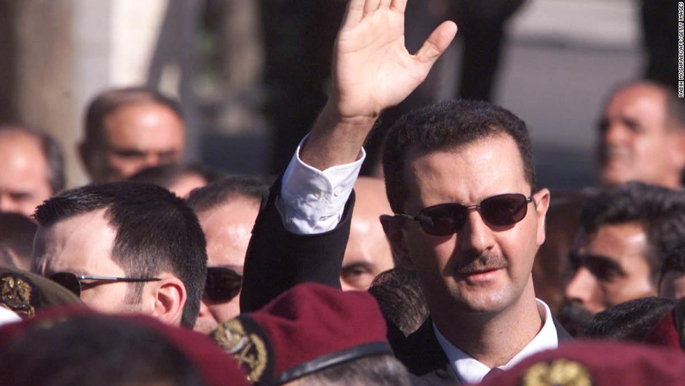 Al-Assad waves to supporters as he marches behind the coffin during his father's funeral in Damascus on June 13, 2000.