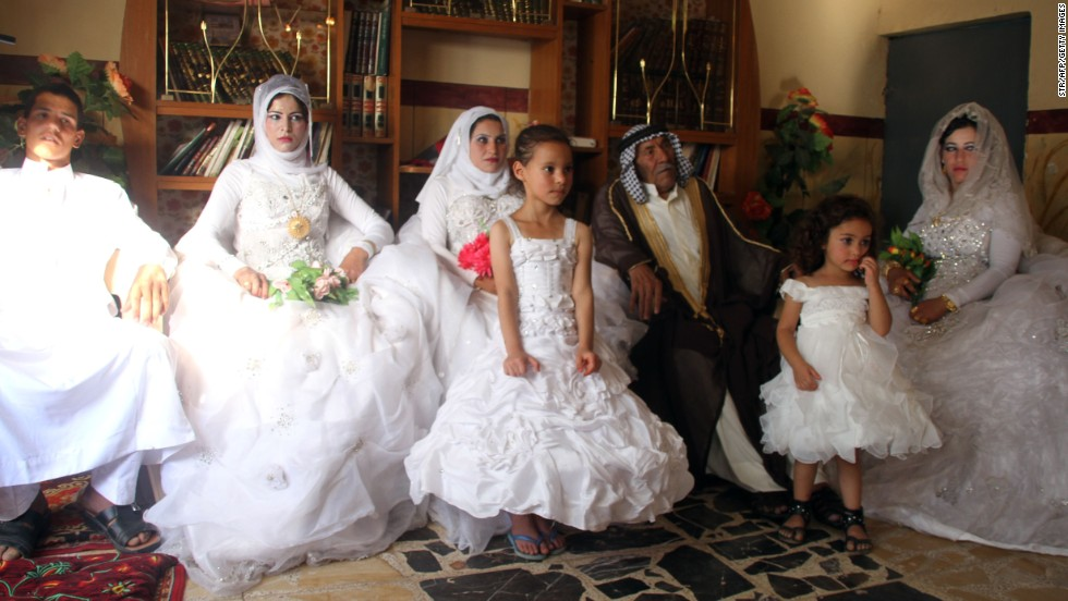Musali Mohammed al-Mujamaie, a 92-year-old Iraqi farmer, sits next to Muna Mukhlif al-Juburi, his new 22-year-old wife, the new wives of his grandsons and one of his grandsons during celebrations after their group wedding in his home village of Gubban, Iraq.