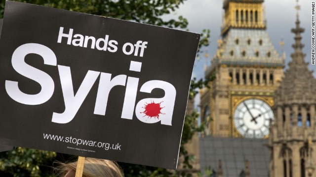 Demonstrators hold placards during a protest against potential British military involvement in Syria at a gathering outside the Houses of Parliament in central London on Thursday, August 29. British Prime Minister David Cameron failed on Thursday, to secure parliament's approval for military intervention in Syria.