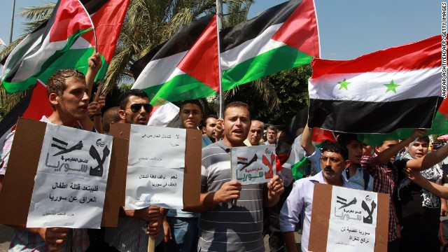 Palestinians, carrying placards and waving the Syrian and Palestinian national flags, gather during a demonstration against military intervention in Syria in the West Bank city of Nablus on August 29.