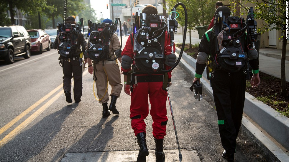"""""""Ghostbusters"""" cosplayers walk toward the staging area for the Dragon Con parade."""