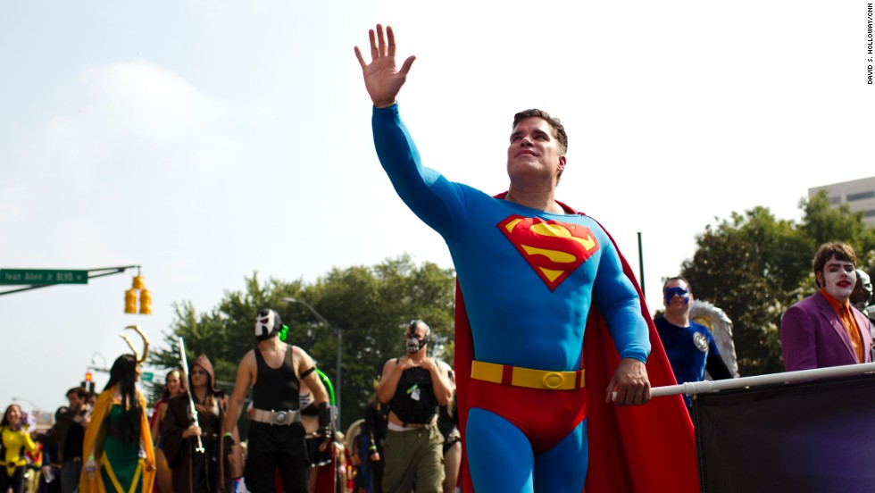A man dressed as Super-Man walks in the parade with other characters from DC Comics.