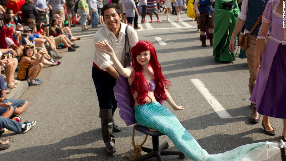 """Ariel, """"The Little Mermaid,"""" gets a little dry-land help moving along the parade route."""