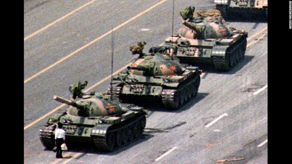 "Following a crackdown that resulted in the deaths of hundreds of student demonstrators in Beijing, a lone Chinese protester steps in front of People's Liberation Army tanks in Tiananmen Squarein 1989. At least five photographers captured the event, which became a symbol of defiance in the face of oppression. Charlie Cole, working for Newsweek, won a World Press Photo Award for his version of the image. The identity and fate of the ""Tank Man"" remains unclear."