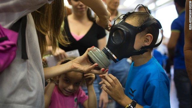 An Israeli woman shows her children how to put on a gas mask as they pick their gas masks at a distribution center on August 26, 2013 in Tel Aviv, Israel
