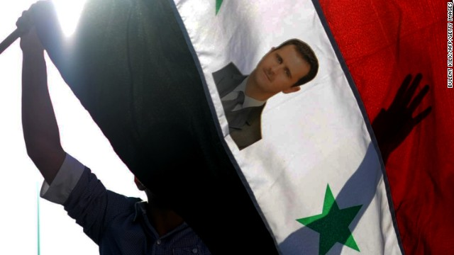 A protester waves a Syrian flag with the photograph of Syrian President Bashar al-Assad during a rally against a possible attack on Syria in response to alleged use of chemical weapons by the Assad government on September 1, 2013, in Hatay.
