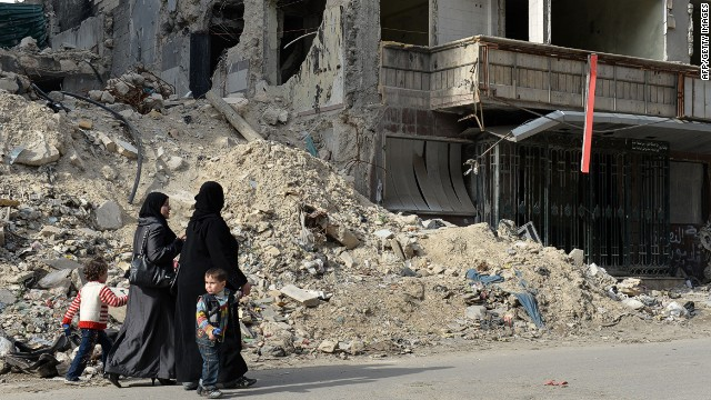 Syrian women walk past the destruction at Dar Al-Shifa hospital in the northern city of Aleppo on on April 21, 2013.