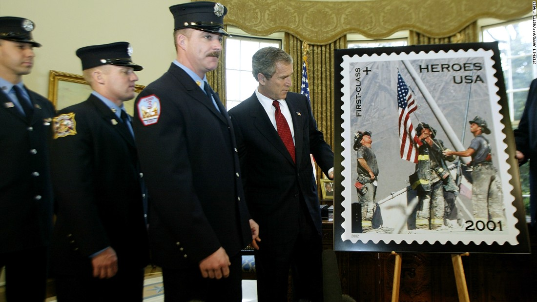 "President George W. Bush unveils a ""Heroes of 2001"" stamp issued by the Postal Service on March 11, 2002, to raise funds to assist the families of emergency relief workers killed or permanently disabled as a result of the World Trade Center attacks. He is joined at the White House by the firefighters who are featured in the image, from left, Eisengrein, Johnson and McWilliams."