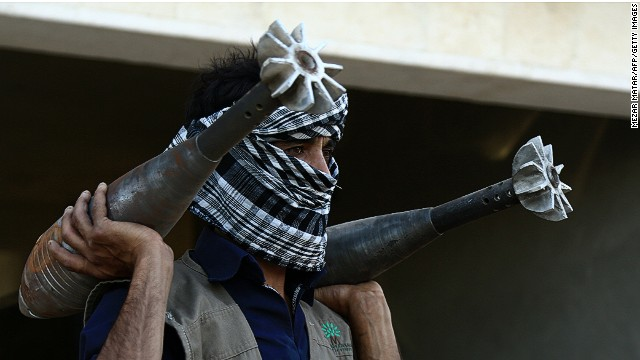 A rebel fightercarries homemade mortar rounds on September 3, 2013 in the northern Syrian city of Raqqa.