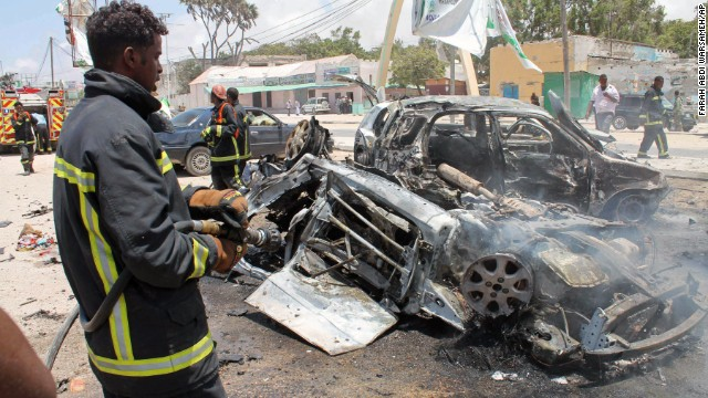 A firefighter sprays water on destroyed cars in Mogadishu, Somalia, Saturday, Sept, 7, 2013.