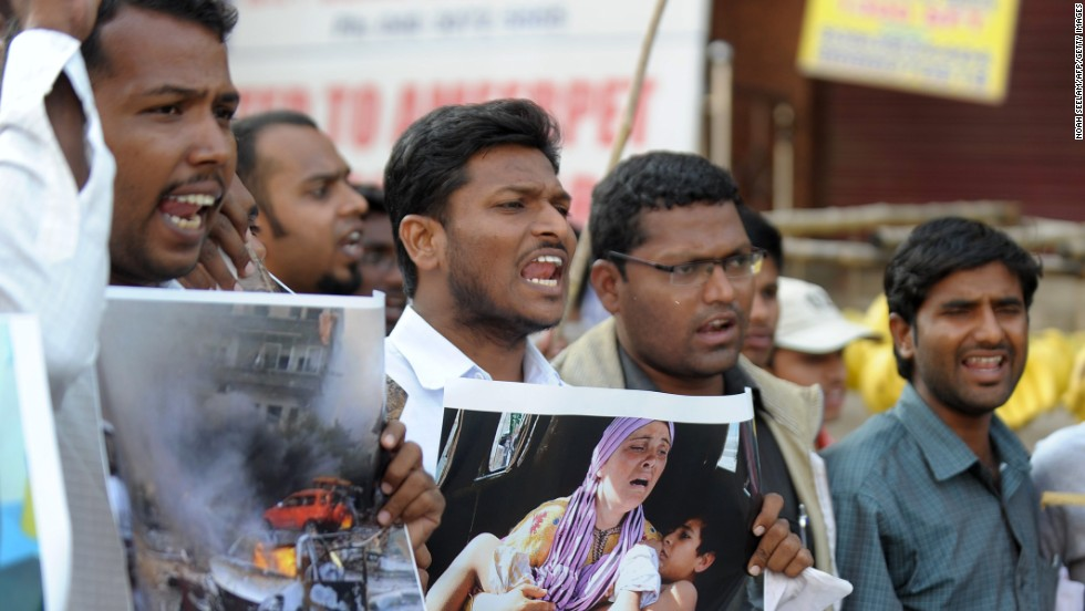 Indian students hold photographs during a protest against military intervention in Syria on Wednesday, September 4, in Hyderabad.