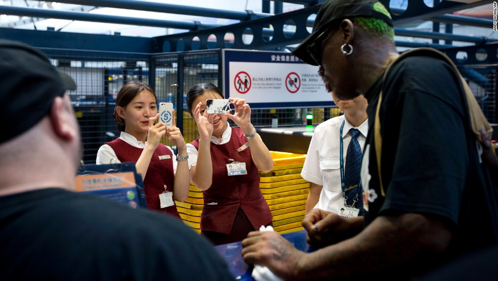 Airport staff take pictures of the former NBA star at a check-in counter at China's Beijing Capital International Airport on September 3 while he was heading to North Korea.