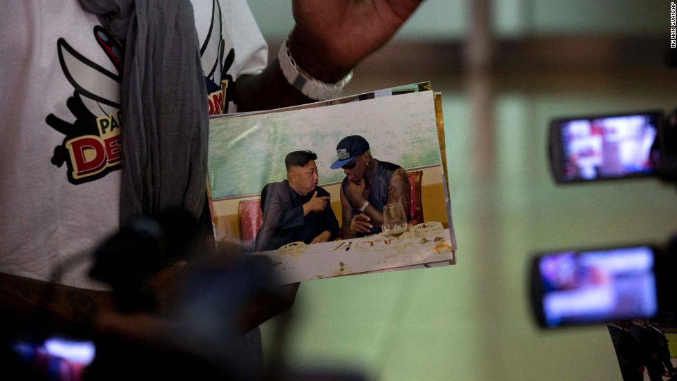"Rodman shows a photo of himself with North Korean leader Kim Jong Un as he arrives at the Beijing airport on September 7. At a news conference Monday, September 9, he called Kim a ""very good guy."""