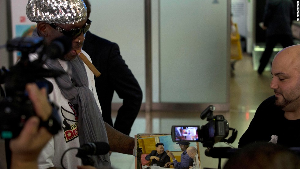 "Rodman shows photos of himself with North Korean leader Kim Jong Un while talking to journalists at the Beijing airport on September 7 after his second trip to the reclusive, nuclear-armed nation. Rodman returned from the communist country announcing he will put together a ""basketball diplomacy"" event with players from North Korea. But he put a damper on any speculation he might have been trying to free imprisoned American Kenneth Bae."