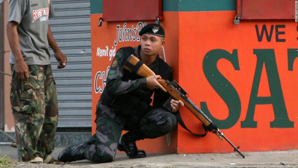 A combat police force sniper gets into position to confront Moro National Liberation Front (MNLF) rebels in downtown Zamboanga City on September 9.
