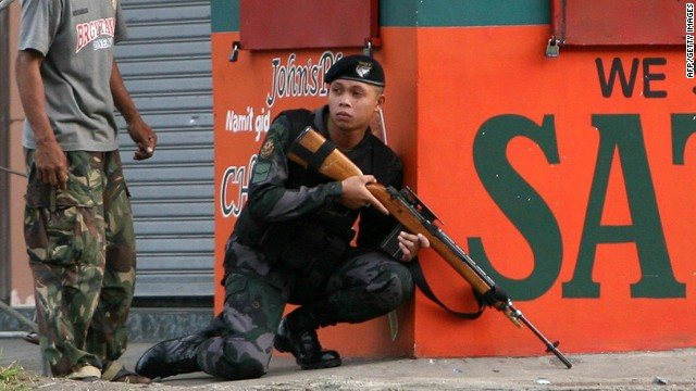 A combat police force sniper gets into position in downtown Zamboanga City in the Philippines on September 9, 2013.