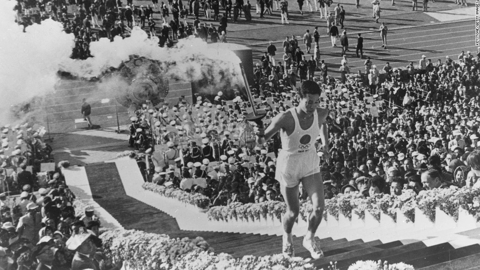 Yoshinori Sakai, a student born in Hiroshima on the day the first atomic bomb devastated the city, carries the torch up the stairs to light the cauldron during the opening ceremony on October 10, 1964.