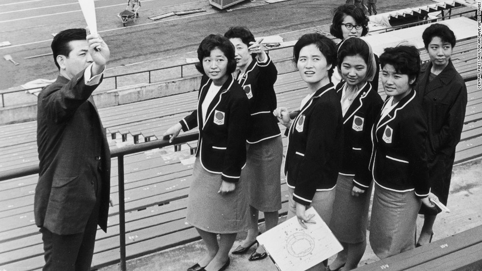 Olympic hostesses receive a briefing from an official at the main stadium in Tokyo, 1964.