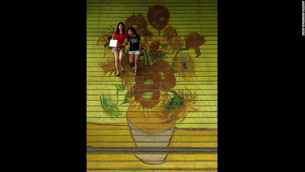 "Shoppers walk down stairs featuring a reproduction of van Gogh's ""Sunflowers"" at the entrance to Ocean Terminal in Hong Kong."