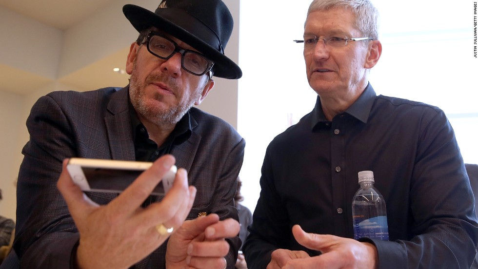 Rocker Elvis Costello, who played a few songs at the event, examines a new iPhone as Tim Cook looks on.