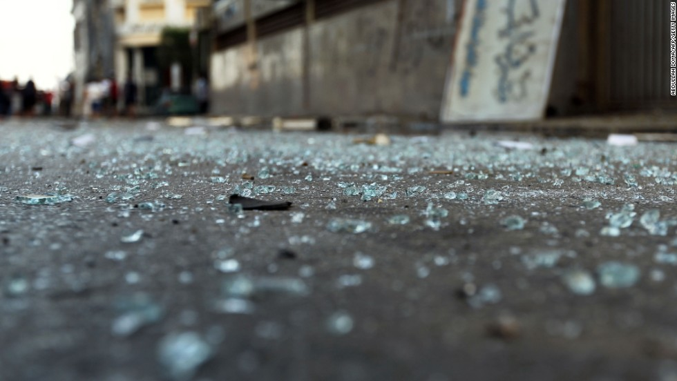 Pieces of glass lay on the ground outside the building.