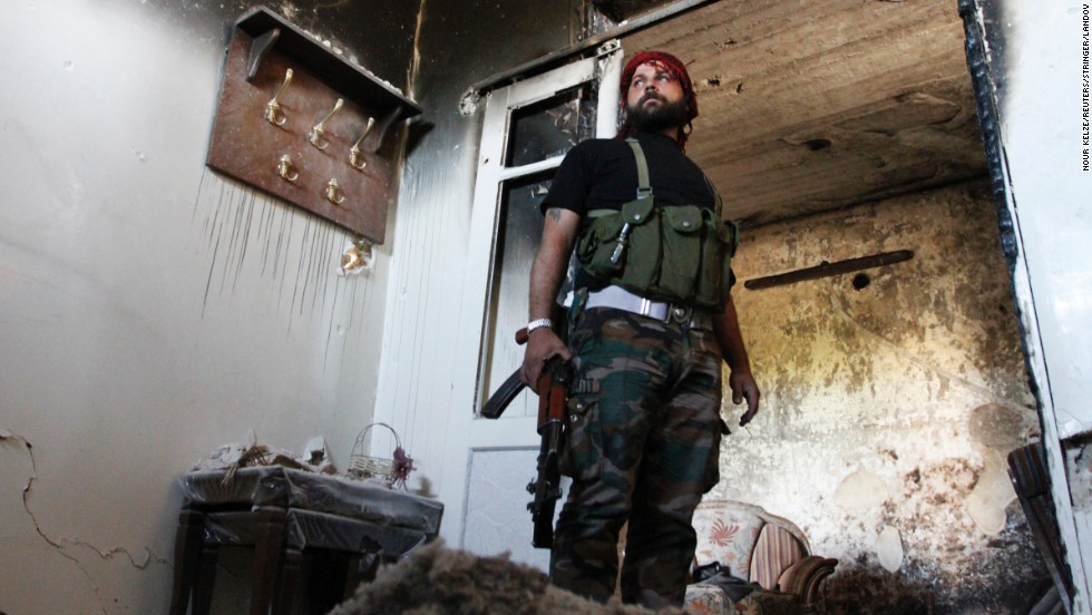 A Free Syrian Army fighter stands guard inside a damaged house in Aleppo's Qastal al-Harami neighborhood on September 11.