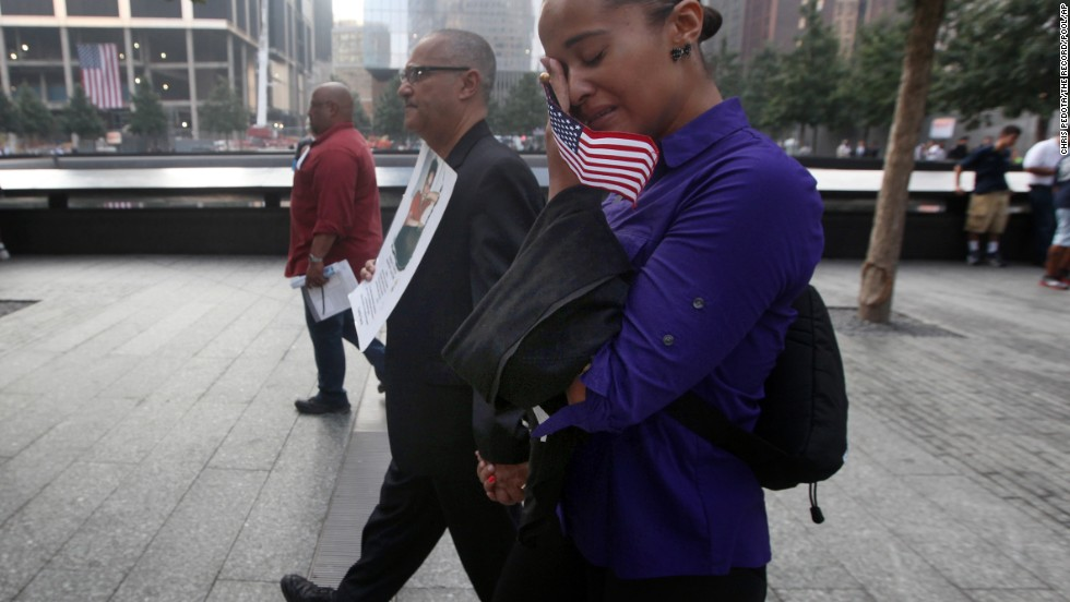 Hector Garcia, center, of Brooklyn, and his daughter Tania attend ceremonies in New York on September 11. Garcia is carrying a photograph of his daughter Marilyn, Tania's sister, who died in the attacks on the World Trade Center.