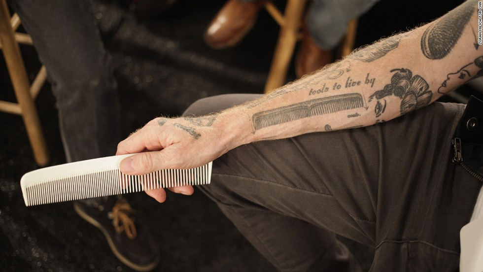 A hairdresser displays his comb tattoo before the Nautica show on September 5, 2013.