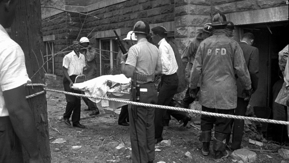 Firefighters and ambulance attendants remove a body from the church.