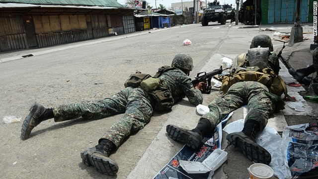 Government soldiers take cover from rebel sniper fire during heavy fighting  in Zamboanga City on September 12, 2013.