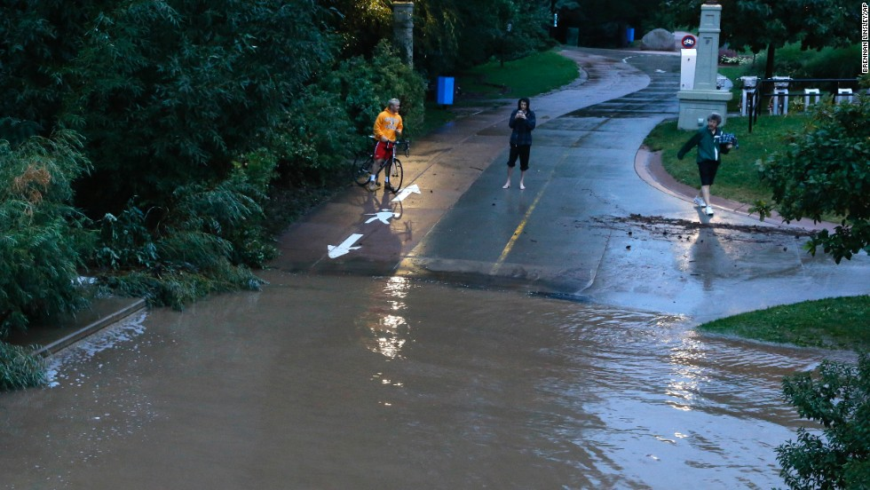 People stand at the edge of floodwaters in Boulder on September 12.