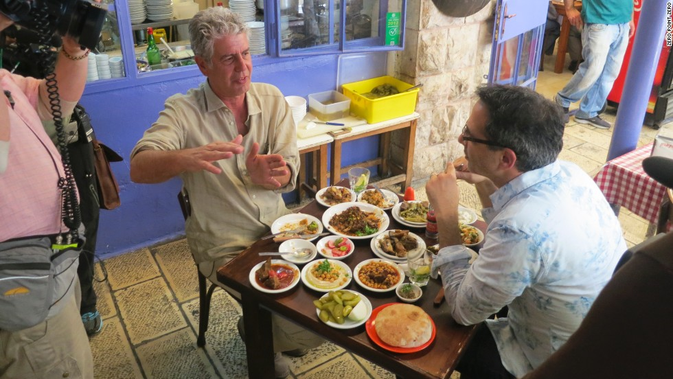 "Bourdain and chef Yotam Ottolenghi enjoy a meal at the restaurant Azura in Jerusalem. No matter your background or life experience, ""you should see this,"" Bourdain said."
