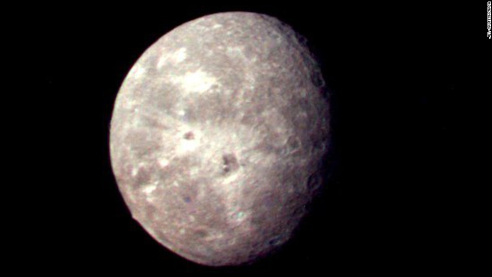 Oberon, Uranus' outermost moon, shows several impact craters on the moon's icy surface.
