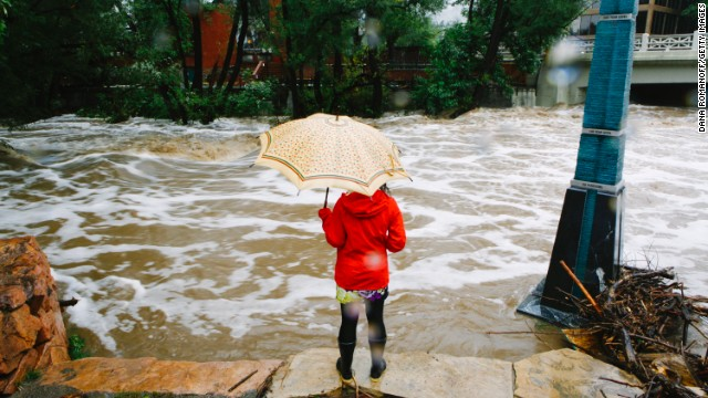 A woman looks at the flooded Boulder Creek in Boulder, Colorado, on Thursday, September 12. An estimated 6-10 inches of rain fell during 12-18 hours along Colorado's Rocky Mountain Range, from Boulder south to Colorado Springs, causing residents to be evacuated, washing out roads and killing at least three people.