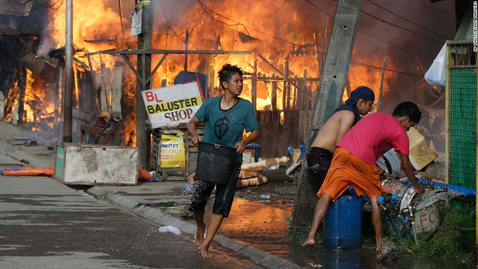 Residents try to put out fire that gutted several homes while government troopers continue their assault at Muslim rebels on September 12 in Zamboanga City.