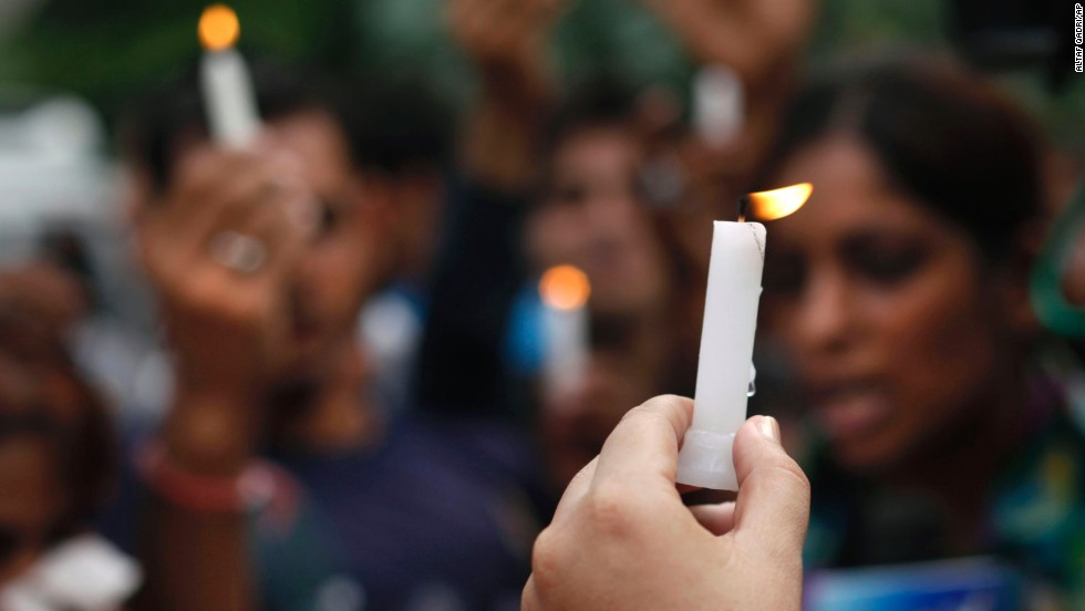 People hold candles outside the courthouse in New Delhi.