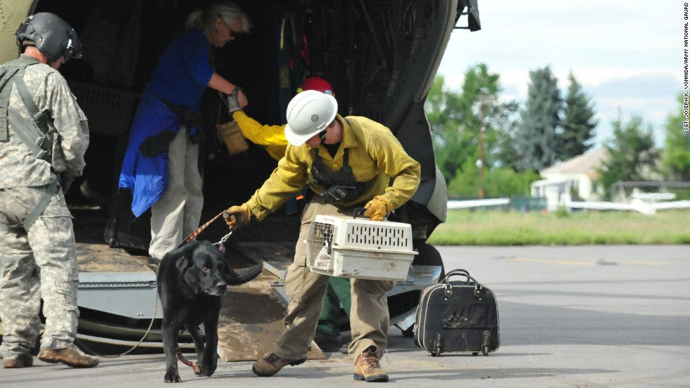 Guardsmen help residents and their pets off a Colorado National Guard Chinook helicopter at the Boulder Municipal Airport on September 13.