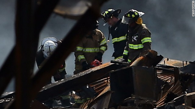 Firefighters walk through the scene of a massive fire that destroyed dozens of businesses along an iconic Jersey shore boardwalk on September 13, 2013 in Seaside Heights, New Jersey.