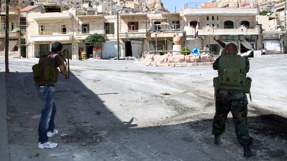 Syrian soldiers take aim at rebel fighters positioned in the mountains of the Christian town of Maalula on September 13.