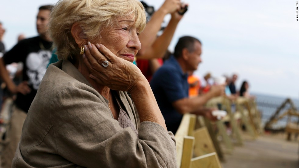 A woman watches as people gather on the Seaside Park boardwalk to look at the destruction  after the massive fire on September 13.