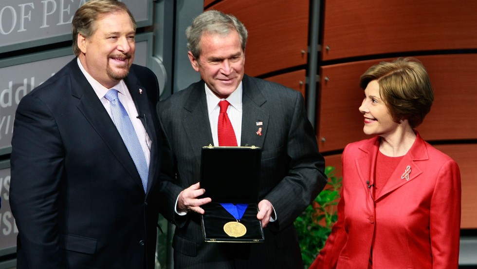 Warren presents President George W. Bush with the International Medal of P.E.A.C.E, as Laura Bush looks on, during the Saddleback Civil Forum on Global Health at the Newseum in Washington on December 1, 2008. The award was in recognition of an initiative to provide funding for treatment for 2 million people with HIV/AIDS by the end of 2008. The acronym P.E.A.C.E. stands for: Promote reconciliation. Equip servant leaders, Assist the poor, Care for the sick, Educate the next generation.