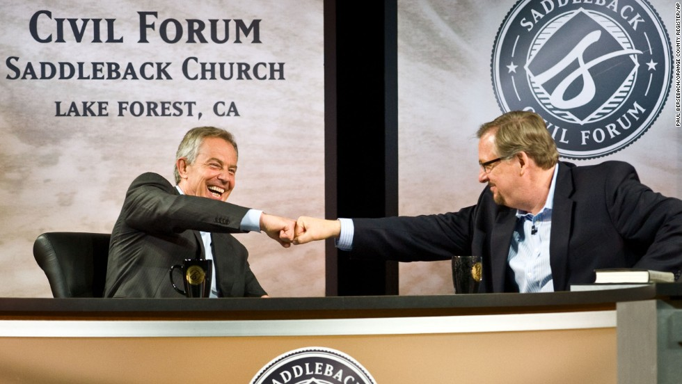 "Former British Prime Minister Tony Blair and Warren fist-bump during the ""Civil Forum on Peace in a Globalized Economy"" at Saddleback Church on March 6, 2011."