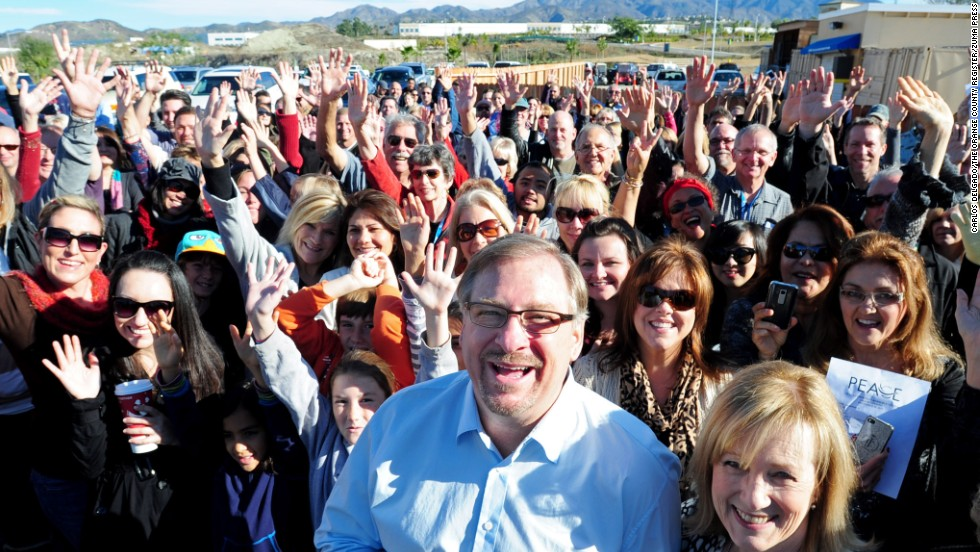 Warren and his wife, Kay, pose with a crowd during the grand opening of the P.E.A.C.E Center at Saddleback Church on December 12, 2011. The center will provide services for low-income families including medical help, counseling, tutoring and food.