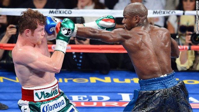Floyd Mayweather Jr., right, throws a left at Canelo Alvarez during their WBC/WBA 154-pound title fight at the MGM Grand Garden Arena on September 14, 2013 in Las Vegas, Nevada.