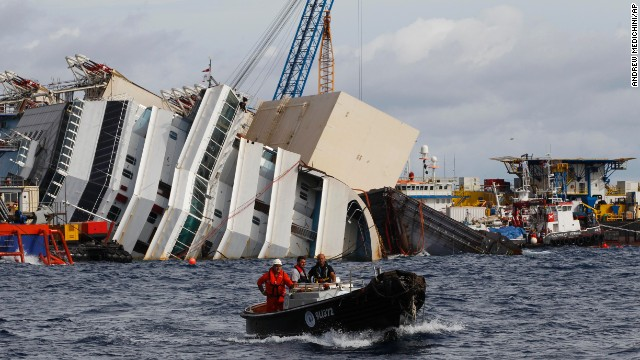 Workmen on a boat sail near the Costa Concordia ship as it lies on its side near the Tuscan Island of Giglio, Italy, Sunday, sept. 15, 2013. An international team of engineers is expected on Monday, Sept. 16 a to try a never-before attempted strategy to right the luxury liner, which capsized after striking a reef in 2012 killing 32 people. (AP Photo/Andrew Medichini)