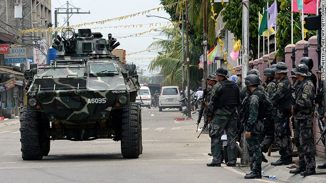 An armored personnel carrier passes by a group of soldiers as clashes between government troops and Muslim rebels continue in the eight-day standoff in Zamboanga City, on the southern island of Mindanao, on September 16, 2013. The Philippine military launched a helicopter assault on September 16 on Muslim rebels occupying parts of a major southern city, stepping up efforts to end an eight-day standoff that has left dozens dead. AFP PHOTO/TED ALJIBETED ALJIBE/AFP/Getty Images
