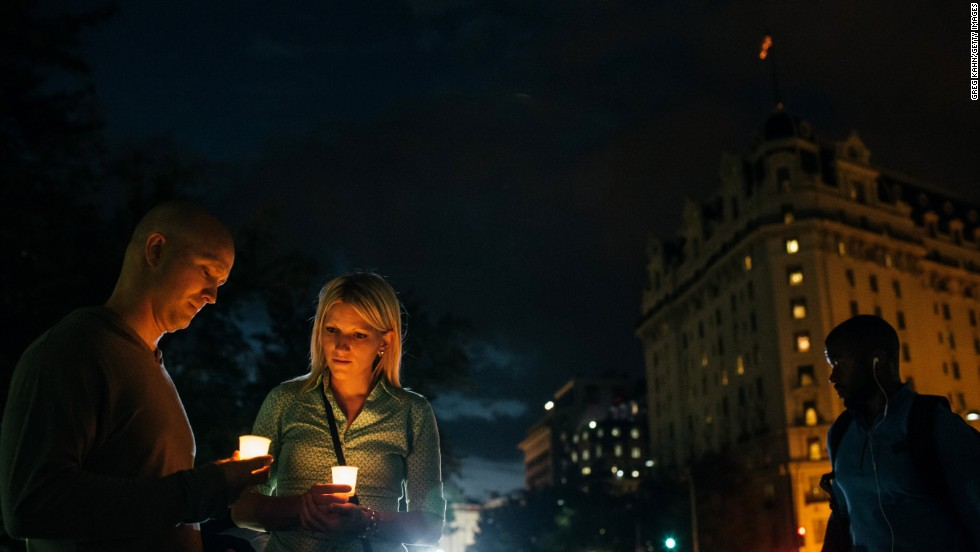 Dave Gray and his wife, Brittany, of Salt Lake City hold candles in remembrance of people affected by gun violence.