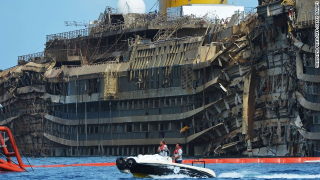 Members of the US salvage company Titan and Italian firm Micoperi pass by the destroyed side of the wreckage of Italy's Costa Concordia cruise ship which begins to emerge from water near the harbour of Giglio Porto. Salvage operators in Italy lifted the Costa Concordia cruise ship upright from its watery grave off the island of Giglio in the biggest ever project of its kind. The ship's horn sounded for the first time since the January 13, 2012 tragedy, its sound mixing with applause and cheers in the port in a dramatic climax to the massive salvage operation. Local residents and survivors spoke of an eerie feeling as the ship rose, saying the sight reminded them of the tragedy that claimed 32 lives.    AFP PHOTO / VINCENZO PINTOVINCENZO PINTO/AFP/Getty Images